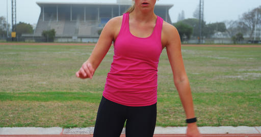 Front view of Caucasian female athlete exercising on race track 4k Live Action