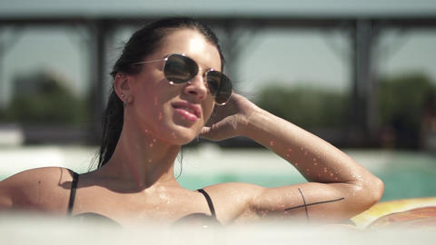 Portrait of adult brunette woman in sunglasses swimming in the pool. Leisure of Footage