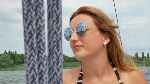 Pretty beautiful girl with light brown hair lies on yacht and sunbathing Footage