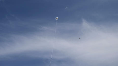 Balloons on long strings in the blue sky Footage
