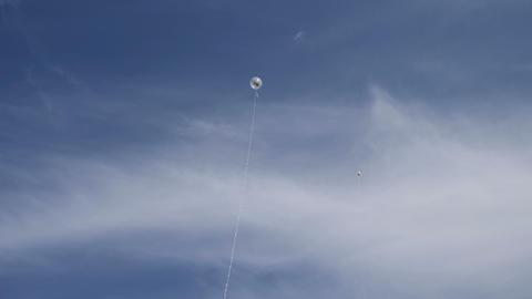 Balloons on long strings in the blue sky ビデオ