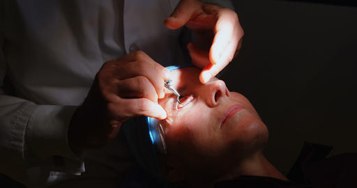 Optometrist examining patient eyes with eye test equipment in clinic 4k Live Action