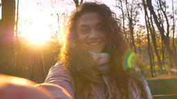 Self-video of smiling caucasian curly-haired woman in sunshine talking in Footage