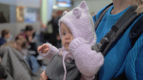 Mum with baby daughter in kangaroo carrier at the airport Live Action