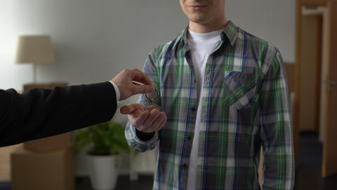 Real estate agent presenting key from new house to young man, youth crediting Live Action