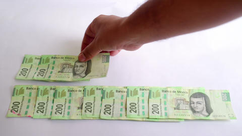 A lot of $200 mexican peso bills are accommodated by a hand. TAKE 2 영상물