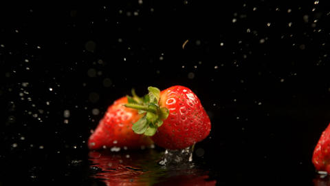 Strawberries falling on water against black background 4k Live Action