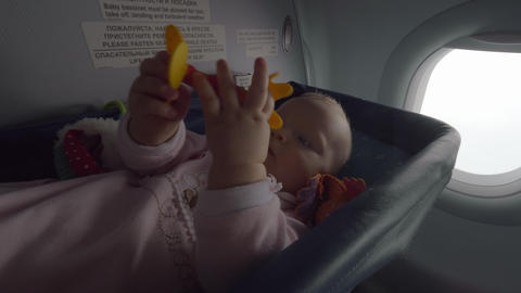 Active baby girl flying by plane in special bassinet Live Action