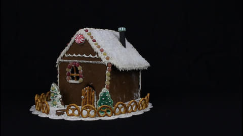 Black cat sniffing gingerbread house Stock Video Footage
