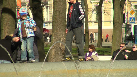 The kid is on the edge of the fountain Stock Video Footage