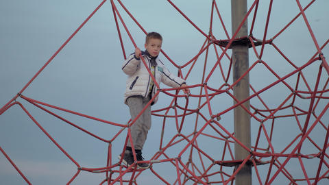 A boy on a red climbing web Footage