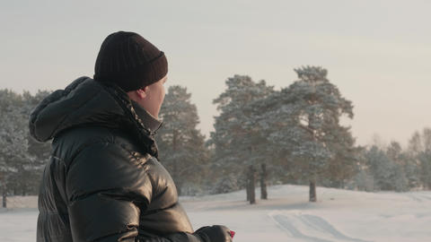 Adult man drinking hot tea on snowy forest landscape at copy space at winter day Footage