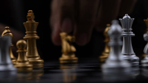 4K Close up shot hands of man playing golden and silver chess select focus Footage
