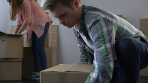 Young couple packing their things in boxes, moving from dormitory to own house Live Action