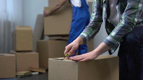 Moving company worker bringing boxes to house, man arriving in new house Live Action
