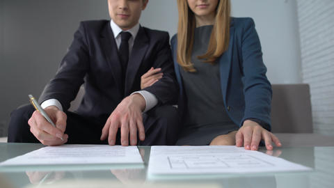 Wealthy couple signing housing purchase contract, real estate agency clients Live Action