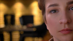 Close-up half-portrait of emotionless young short-haired woman watching into Footage