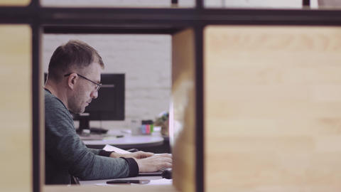 A businessman is sitting at his office desk, working intently on the computer Footage