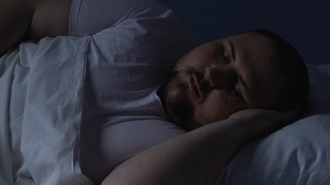 Overweight man sleeping in bed at night, resting on comfortable pillow, dreams Footage