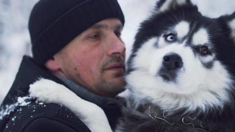 Portrait of a man in winter outerwear hugging and talking to a husky outdoors 영상물