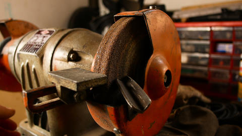 craftsman uses an electric wheel to grind a metal rod in his home workshop GIF