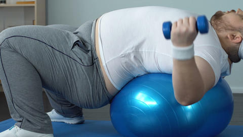 Chubby bachelor making arms exercises dumbbells lying on ball, burning calories Live Action