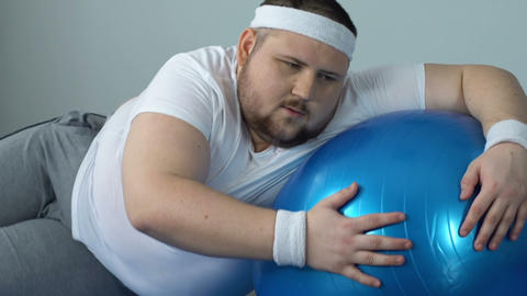 Exhausted fat man falling down on floor with fitness…, Live Action