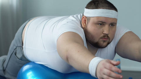 Purposeful fat male doing static exercise lying on fitness ball, desire to sport Live Action