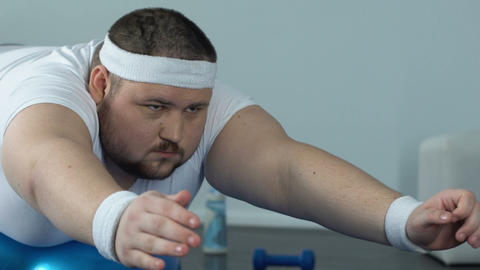 Obese man relaxing fitness ball after home workout complex, power and endurance Live Action
