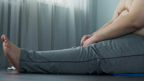 Overweight man stretching muscles sitting on floor, training at home, recovery Live Action