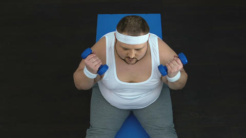 Active fat man raising hands up with dumbbells, weight loss success, motivation Live Action