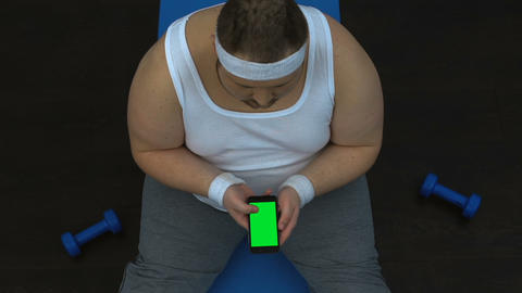 Fat man sportswear watching fitness guide exercises on smartphone, sport blog Live Action