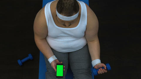 Obese man lifting dumbbell and watching fitness video smartphone, green screen Live Action