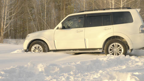 Couple drives off the snow covered forest in a SUV Live Action