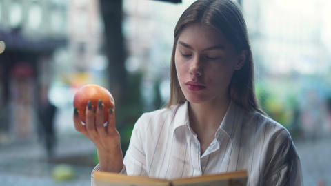 Portrait of beautiful healthy girl eating an apple and attentively reading a Live Action