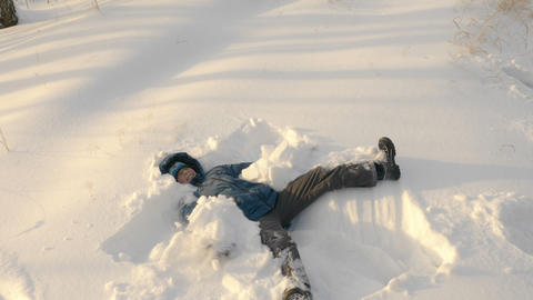 Teenager making snow angel lying down on snow Live Action