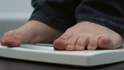 Fat male legs in jeans standing on scales, everyday weight measuring, body care Footage