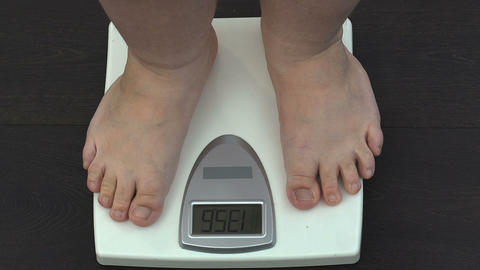 Obese man measuring weight on scales at home, slimming training program, health Live Action