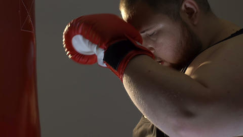 Tired gym customer in boxing gloves leaving sport club, reducing stress activity Footage