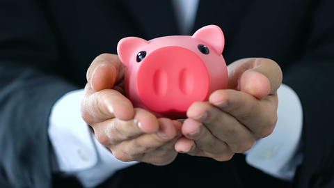 Male hands holding out piggy bank, money saving concept, company budget, finance Footage