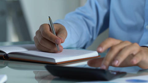 Scrupulous father calculating monthly family budget, making notes in notebook Live Action