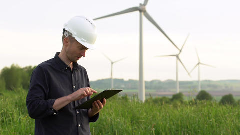 Worker stands near white wind turbines, typing on a tablet. Windmills, green GIF