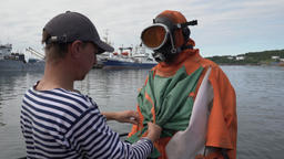 Sailor helps to put on dry diving suit to scuba diver before diving into sea Footage