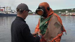 Sailor unties, helps to take off dry diving suit to scuba diver after diving Footage