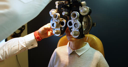 Optometrist examining patient eyes with phoropter 4k Live Action