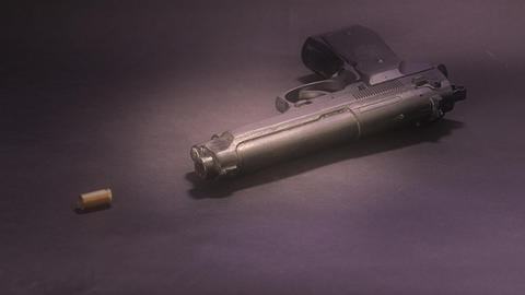 Bullet casings falling in slow motion around handgun,…, Live Action