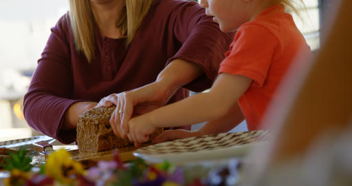 Mother and son cutting loaf of bread on dining table 4k Live Action