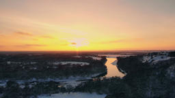 Sunset over frozen river and evergreen forest. Country highway passing across 영상물