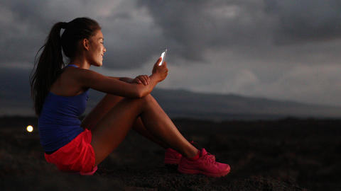 Phone - Woman using smart phone looking at fitness tracking app running at night Footage
