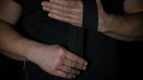 man wraps his hands in black textile bandage for sports Archivo